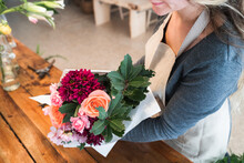 Crop Unrecognizable Young Female Florist With Long Wavy Hair In Casual Clothes And Apron Arranging Elegant Bouquet Of Roses And Assorted Flowers In Store