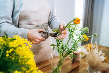 Crop Unrecognizable Young Female Florist In Casual Clothes Cutting Stems Of Fresh Bright Flowers With Pruning Snips While Arranging Bouquet In Glass Vase