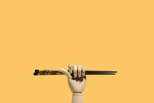 Creative Wooden Hand With Ornamental Bamboo Chopsticks For Asian Food On Orange Background In Studio