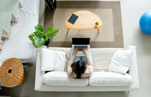 High Angle Of Anonymous Female Browsing Internet On Portable Computer With Black Screen While Resting On Sofa At Home