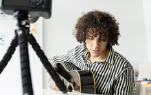 Young Tattooed Male Guitarist Playing Acoustic Guitar While Recording Video On Photo Camera In House Room