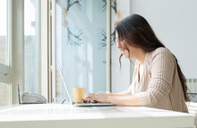 Side View Of Young Female Surfing Internet On Netbook Near Cup Of Hot Drink In Flat