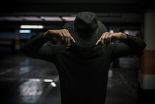 Unrecognizable African American Male Touching Trendy Hat While Standing In Dark Underground Parking