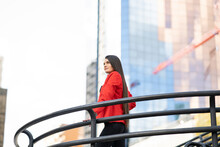 Low Angle Of Female Wearing Elegant Clothes And High Heeled Shoes Standing Near Railing In Downtown And Looking Away