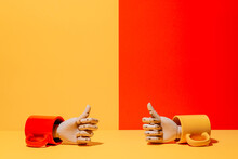Creative Ornamental Wooden Hand With Thumbs Up Inside Colorful Mug On Yellow And Red Background In Studio