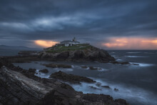 Breathtaking Scenery Of Rocky Island With Lighthouse Located In Ocean Near Rocky Coast In Faro Tapia De Casariego In Asturias In Spain Under Cloudy Sky At Sunrise