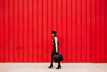 Side View Of Female Entrepreneur Wearing Trendy Clothes Walking Along Street On Background Of Red Wall And Looking At Camera