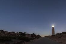 Lighthouse With Bright Lights Placed On Sandy Beach In Faro De Trafalgar In Cadiz In Spain Under Night Sky With Stars