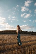 Peaceful Female In Elegant Dress Standing On Dry Field In Rural Area And Looking At Camera