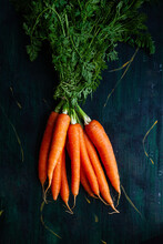 Top View Of Bunch Of Whole Raw Carrots With Stems And Leaves On Wooden Surface