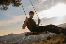Bearded Male In Black Apparel Looking At Camera While Sitting On Swing Against Mountains In Town At Sundown