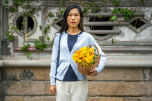 Beautiful Asian's Girl Portrait While She Carries A Wicker Basket With Yellow Flowers.