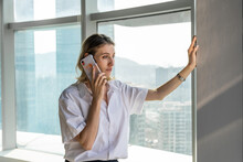 Young Businesswoman Standing In Office With Big Windows Having A Phone Call On The Mobile Phone