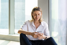 Delight Young Woman Sitting In Empty Office With Big Window Browsing On The Mobile Phone
