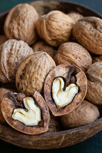 Round Shaped Wooden Bowl Full Of Crunchy Walnuts With Dry Uneven Nutshells On Table