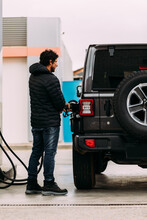 Side View Of A Man Refueling His Off-road Car At A Gas Station