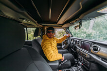 Inside View Of A Driver Wearing A Cap And Sunglasses In An Off-road Car Looking At Camera