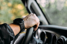 Crop View Of Anonymous Man With Her Hand On A Car Steering Wheel On Blur Background