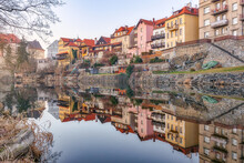 Picturesque View Of Aged Shabby Residential Buildings Reflecting In Calm Water Of River