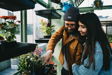 Content Stylish Couple Embracing In Greenhouse While Standing Near Shelf And Picking Blooming Potted Flower