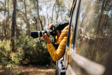 Side View Of An Adventurous Photographer Taking Photos From Inside His Off-road Car