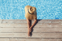 Enjoying Summer Vacation. Beautiful Tan Woman In Hat Relaxing In Pool Water At Wooden Pier, View Above. Slim Young Female Sunbathing At Swimming Pool Edge At Tropical Resort. Travel And Holidays
