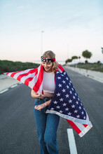 Delighted American Female Standing Wrapped With National USA Flag On Roadway At Sunset And Looking Down