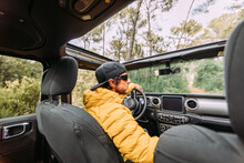 From Behind Inside View Of A Driver Wearing A Cap And Sunglasses In An Off-road Car Looking Away