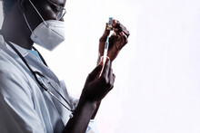 Ethnic Doctor Filling In Syringe From Bottle With Vaccine Preparing To Vaccinate Patient In White Background In A Clinic During Coronavirus Outbreak