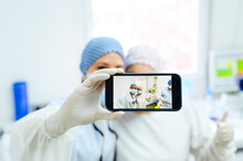Anonymous Female Doctors In Uniforms With Thumb Up Taking Self Portrait On Cellphone In Hospital