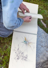From Above Of Crop Anonymous Male Artist Turning Page Of Album With Sketches In Nature