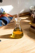 Glass Jar With Natural Aromatic Olive Oil Placed On Wooden Table In Home Kitchen