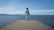 Back View Anonymous African American Female In White Clothes Standing On Wooden Quay Near Vast Rippling Lake Under Clear Blue Sky In Summer Nature