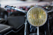 Closeup Of Yellow Headlight Of Old Fashioned Motorbike Placed Against Blurred Background Of Workshop