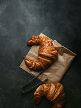 Top View Composition With Tasty Fresh Crusty Croissants Placed With Paper Bag And Metal Tongs On Black Background