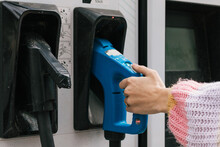 Crop Anonymous Female Taking Electric Charger For Recharging Battery Of EV Automobile From Panel On Charging Station