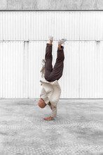 Unrecognizable Male Dancer Showing Breakdance Movement While Balancing On Arms And Performing Hand Hops On Concrete Ground In Urban Area