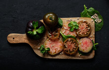 Top View Of Fresh Ripe Sliced Black Tomatoes And Green Mint Stems On Wooden Cutting Board On Black Background