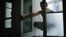 Pensive Male Sitting On Knees On Windowsill At Home
