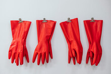 Composition Of Red Rubber Gloves Hanging On Clothes Pins On White Background In Studio