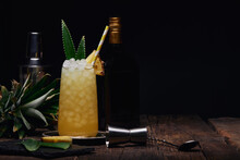 Glass Of Alcoholic Cocktail Decorated With Pineapple Piece And Leaves With Paper Straw On Tray Near Shaker And Bottle With Shot Glass At Table On Black Background