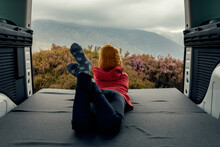 Back View Of Unrecognizable Traveling Teenager Lying In Van And Enjoying View Of Highlands During Trip