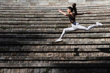 Side View Of Fit Female In Sportswear Jumping In Splits Above Stone Stairs While Warming Up Body Before Yoga Session