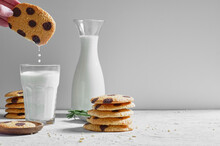 Crop Anonymous Person Dipping Delicious Sweet Homemade Cookies With Chocolate Chips Into Glass Of Fresh Milk