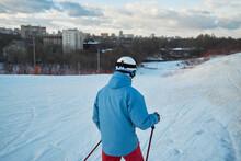 Back View Anonymous Male Skier In Warm Sportswear Skiing Along Snowy Hill Slope In Winter City Park