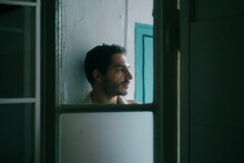 Calm Shirtless Male With Beard Leaning On Shabby Wall At Home And Looking Away