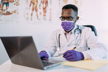 African American Doctor In Eyeglasses Working With Online Patient On Netbook While Writing In Patient File At Table In Hospital
