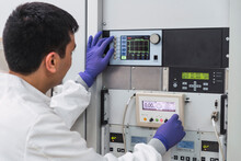Crop Concentrated Professional Male Laboratory Assistant In White Robe And Latex Gloves Pressing Buttons On Modern Equipment