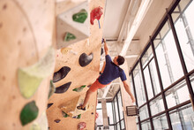 Low Angle Of Muscular Male Alpinist Hanging On Climbing Wall While Training In Bouldering Center