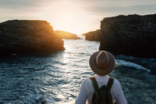 Man With Backpack And Hat Standing And Looking At The Sea